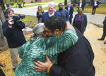Lowndes County resident Charlie Mae Holcombe hugs the Rev. William Barber II, leader of the Moral Mondays movement, as former U.S. Vice President Al Gore, founder of the Climate Reality Project, looks on during a visit to talk about the failing wastewater sanitation system at her home Thursday, Feb. 21, 2019, in Hayneville, Ala. (AP Photo/Julie Bennett)