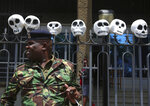 A Kenyan policeman stands guard as fake skulls are placed on a fence of the Kenya Foreign Affairs office in Nairobi, Kenya as South Sudanese and Kenyan activists, some carrying mock skulls, protest against South Sudanese officials allegedly benefiting from the civil war and laundering money through Kenyan banks, in downtown Nairobi, Kenya Thursday, Oct. 11, 2018. Activists and refugees pressured Kenya's government to act against South Sudanese officials who have been sanctioned by the United Nations and are thought to be living freely in Kenya. (AP Photo/Brian Inganga)