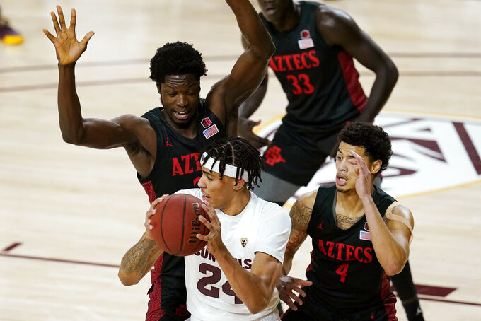 San Diego State forward Nathan Mensah, left, and guard Trey Pulliam (4) defend against Arizona State forward Jalen Graham, front, during the first half of an NCAA college basketball game Thursday, Dec. 10, 2020, in Tempe, Ariz. (AP Photo/Ross D. Franklin)