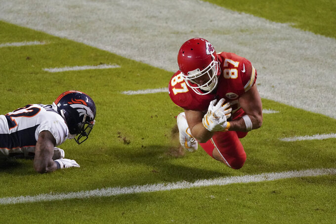 Kansas City Chiefs tight end Travis Kelce (87) scores on a 20-yard touchdown reception as Denver Broncos strong safety Kareem Jackson (22) defends in the second half of an NFL football game in Kansas City, Mo., Sunday, Dec. 6, 2020. (AP Photo/Charlie Riedel )