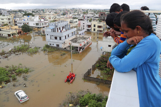 Residents look at a street inundated with floodwater after heavy rainfall in Hyderabad, India, India, Wednesday, Oct. 14, 2020. Record rains and heavy flooding in the southern Indian state of Telangana collapsed houses and killed more than a dozen people, police said Wednesday. (AP Photo/Mahesh Kumar A.)