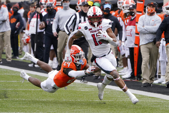 Texas Tech wide receiver Erik Ezukanma (13) carries past Oklahoma State cornerback Jarrick Bernard-Converse (24) for a touchdown in the second half an NCAA college football game in Stillwater, Okla., Saturday, Nov. 28, 2020. (AP Photo/Sue Ogrocki)
