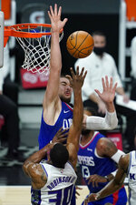 Sacramento Kings forward Glenn Robinson III (30) takes a shot against Los Angeles Clippers center Ivica Zubac, top, during the fourth quarter of an NBA basketball game Wednesday, Jan. 20, 2021, in Los Angeles. (AP Photo/Ashley Landis)