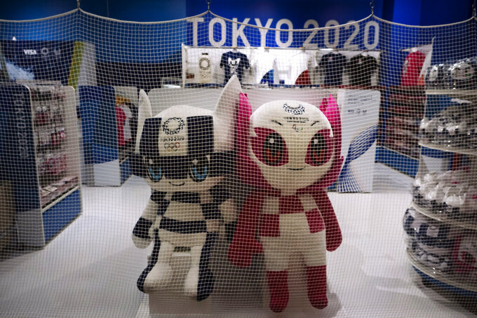 In this April 2, 2020, photo, a net is laid around a Tokyo 2020 merchandise store after the shop closed for the day at the Narita International Airport in Nairta, near Tokyo. Official Tokyo Olympic souvenir shops are drawing few customers these days. The pandemic and the fact the Olympics have been postponed for a year has wiped out almost all business.  (AP Photo/Jae C. Hong, File)