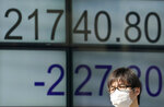 A man walks past an electronic stock indicator of a securities firm in Tokyo, Wednesday, March 14, 2018. Asian shares fell Wednesday, taking their cue from a dip on Wall Street after the abrupt departure of U.S. Secretary of State Rex Tillerson. Concern over tariff hikes announced by President Donald Trump was weighing on sentiment. (AP Photo/Shizuo Kambayashi)