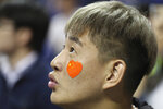 A fan with a heart-shaped Chinese national flag sticker on his face watches a preseason NBA basketball game between the Brooklyn Nets and Los Angeles Lakers at the Mercedes Benz Arena in Shanghai, China, Thursday, Oct. 10, 2019. (AP Photo)