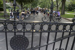 Protesters march beyond a gate on a private street to bring attention to racial injustice, Friday, July 3, 2020, in St. Louis. (AP Photo/Jeff Roberson)