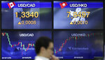 An employee of the bank watches the computer monitors near the screens showing the foreign exchange rates at the foreign exchange dealing room in Seoul, South Korea, Monday, March 18, 2019. Asian shares were mixed Monday as investors continued to watch for signs the U.S. and China could be making progress on critical negotiations aimed at resolving a trade war between the world's two biggest economies.(AP Photo/Lee Jin-man)