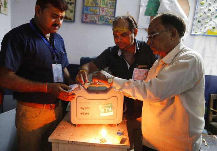 Election officers seal an electronic voting machine at the end of polling in Varanasi, India, Sunday, May 19, 2019. Indians voted in the seventh and final phase of national elections, wrapping up a 6-week-long long, grueling campaign season with Prime Minister Narendra Modi's Hindu nationalist party seeking reelection for another five years. Counting of votes is scheduled for May 23. (AP Photo/Rajesh Kumar Singh)