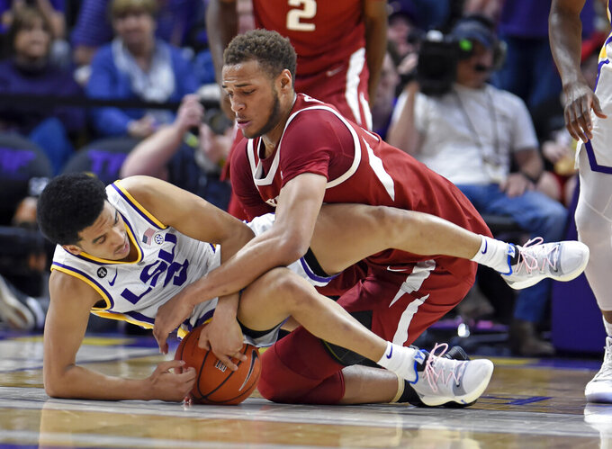 LSU guard Tremont Waters (3) and Arkansas forward Daniel Gafford (10) scramble for the ball during the first half of an NCAA college basketball game Saturday, Feb. 2, 2019, in Baton Rouge, La. (AP Photo/Bill Feig)
