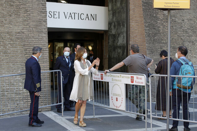 Vatican Museum director Barbara Jatta, center, stands outside the museum entrance to welcome back the first visitors on the museum's reopening date, in Rome, Monday, June 1, 2020. The Vatican Museums reopened Monday to visitors after three months of shutdown following COVID-19 containment measures. (AP Photo/Alessandra Tarantino)