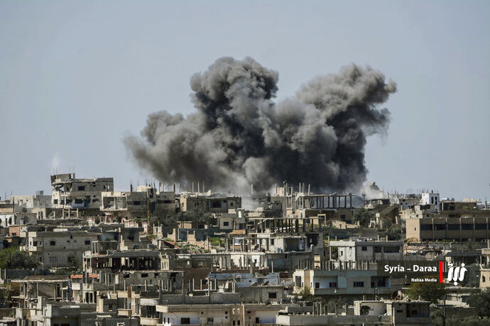 FILE - This Thursday, July 5, 2018 file photo provided by Nabaa Media, a Syrian opposition media outlet, shows smoke rising over buildings that were hit by Syrian government forces bombardment, in Daraa province, southern Syria. Syrian activists and state media said Thursday, July 12, 2018 that the rebels have agreed to surrender Daraa, the first city to revolt against President Bashar Assad with Arab Spring-inspired protests seven years ago, to government forces. (Nabaa Media via AP, File)