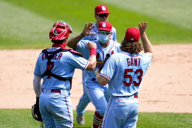 St. Louis Cardinals catcher Andrew Knizner, left, and relief pitcher John Gant fake a high five with Kolten Wong after the Cardinals 5-1 win over the Chicago White Sox in Game 1 of a double-header baseball game Saturday, Aug. 15, 2020, in Chicago. (AP Photo/Charles Rex Arbogast)