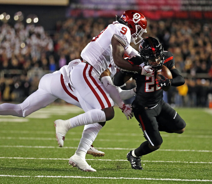 Texas Tech's Ta'Zhawn Henry (26) is tackled by Oklahoma's Kenneth Murray (9) during the first half of an NCAA college football game Saturday, Nov. 3, 2018, in Lubbock, Texas. (AP Photo/Brad Tollefson)