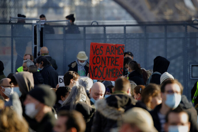 Demonstrators gather during a protest against bill on police images, in Paris, Saturday, Nov. 21, 2020. Thousands of people took to the streets in Paris and other French cities Saturday to protest a proposed security law they say would impinge on freedom of information and media rights. The board reads: Your guns against our cameras. (AP Photo/Christophe Ena)
