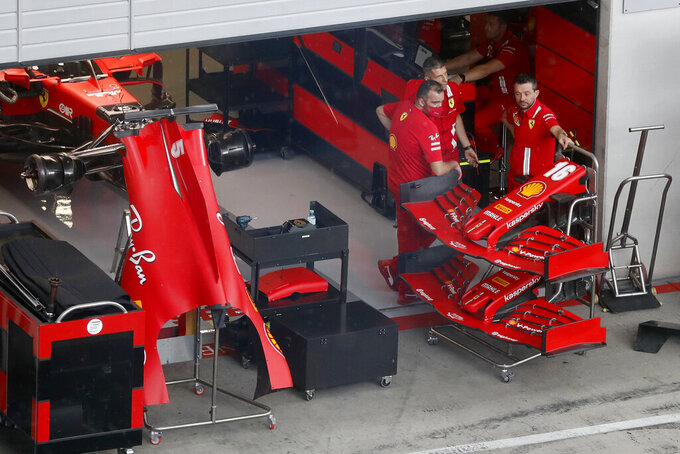 Ferrari technicians pause as they work on Sebastian Vettel's car the at the Red Bull Ring racetrack in Spielberg in Spielberg, Austria, Thursday, July 2, 2020. Austrian Formula One Grand Prix will be held on Sunday. (AP Photo/Darko Bandic)