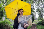 In this Friday, April 19, 2019, photo Katrina Spade, the founder and CEO of Recompose, displays a sample of the compost material left from the decomposition of a cow, left, and some of the combination of wood chips, alfalfa and straw used in the process, as she poses for a photo in Seattle. (AP Photo/Elaine Thompson)