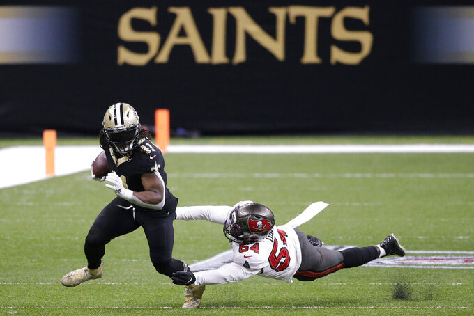 New Orleans Saints running back Alvin Kamara (41) runs past Tampa Bay Buccaneers inside linebacker Lavonte David (54) during the first half of an NFL divisional round playoff football game, Sunday, Jan. 17, 2021, in New Orleans. (AP Photo/Butch Dill)