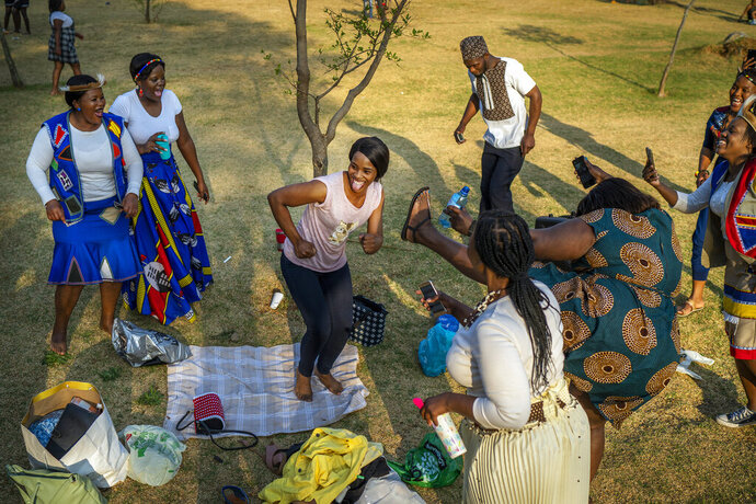 People celebrate South Africa's Heritage Day by dancing at Zoo Lake park in Johannesburg Thursday Sept. 24, 2020. As the number of worldwide Covid-19 death is nearing the million mark, coronavirus related case numbers and deaths in South Africa hit the lowest in months. (AP Photo/Jerome Delay)