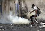 Riot police fire tear gas during clashes between Iraqi security forces and anti-government demonstrators, in downtown Baghdad, Iraq, Wednesday, Nov. 13, 2019. (AP Photo/Hadi Mizban)
