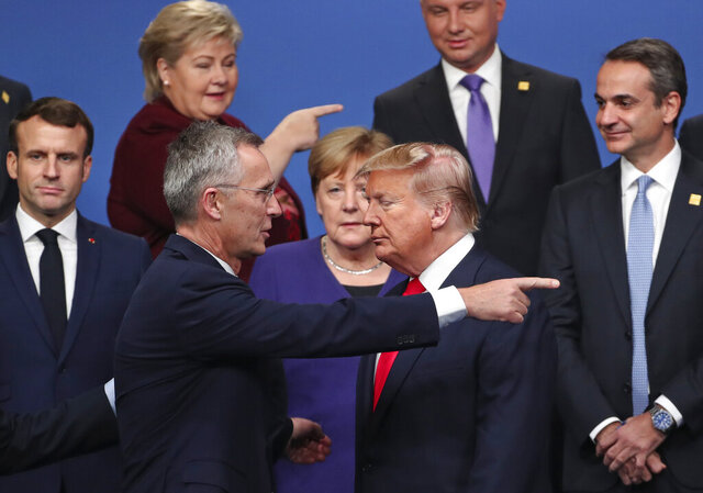 FILE - In this Dec. 4, 2019, file photo, NATO Secretary General Jens Stoltenberg, center front left, speaks with U.S. President Donald Trump, center front right, after a group photo at a NATO leaders meeting at The Grove hotel and resort in Watford, Hertfordshire, England. From left, French President Emmanuel Macron, Norway's Prime Minister Erna Solberg, German Chancellor Angela Merkel, Poland's President Andrzej Duda and Greek Prime Minister Kyriakos Mitsotakis. World leaders including Macron, Merkel, Solberg and Stoltenberg, are condemning the storming of the U.S. Capitol by supporters of President Donald Trump.(AP Photo/Francisco Seco, File)
