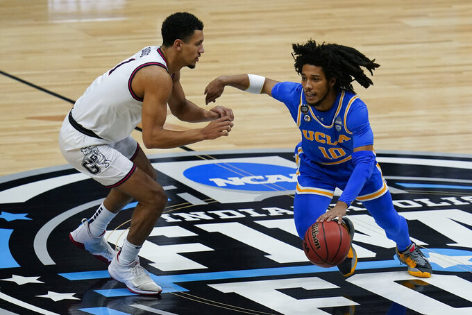 UCLA guard Tyger Campbell (10) drives up court ahead of Gonzaga guard Jalen Suggs (1) during the first half of a men's Final Four NCAA college basketball tournament semifinal game, Saturday, April 3, 2021, at Lucas Oil Stadium in Indianapolis. (AP Photo/Michael Conroy)