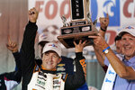 AJ Allmendinger, left, is presented with his trophy after winning a NASCAR Xfinity Series auto race at Bristol Motor Speedway Friday, Sept. 17, 2021, in Bristol, Tenn. (AP Photo/Mark Humphrey)
