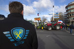 A farmer wearing the Farmers Defense Force jacket stands at an intersection blocked by tractors in The Hague, Netherlands, Wednesday, Feb. 19, 2020. Dutch farmers, some driving tractors, poured into The Hague on Wednesday to protest government moves to rein in carbon and nitrogen emissions to better fight climate change. (AP Photo/Peter Dejong)