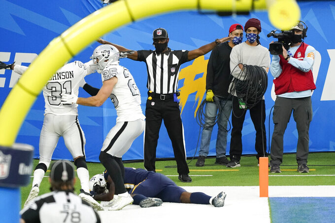 Los Angeles Chargers wide receiver Mike Williams, below, stays down on the field after an injury and an incomplete pass in the end zone during the second half of an NFL football game against the Las Vegas Raiders, Sunday, Nov. 8, 2020, in Inglewood, Calif. (AP Photo/Ashley Landis)