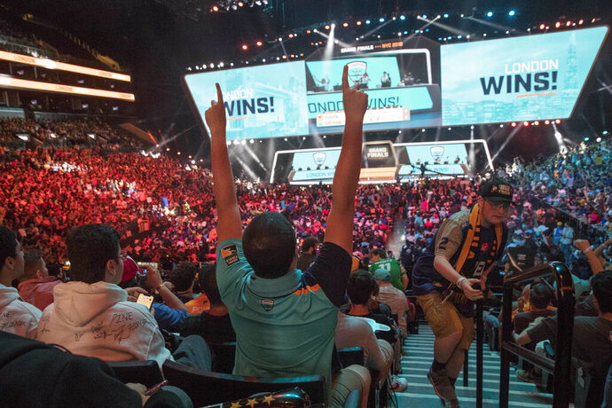 FILE - In this July 28, 2018, file photo, London Spitfire fan Rick Ybarra, of Plainfield, Ind., reacts after London won the second game against the Philadelphia Fusion during the Overwatch League Grand Finals competition at Barclays Center in New York. A new venture backed by many of video gaming's biggest publishers is unveiling a network that hopes to be to esports what ESPN has been to traditional sports. VENN is set to launch in 2020 and aims to give the fragmented esports scene a home base for content with higher production value than gamers are used to with online streaming. (AP Photo/Mary Altaffer, File)