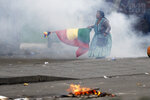 A supporter of former President Evo Morales holds a Bolivian flag during clashes with police in La Paz, Bolivia, Wednesday, Nov. 13, 2019. Bolivia's new interim president Jeanine Anez faces the challenge of stabilizing the nation and organizing national elections within three months at a time of political disputes that pushed Morales to fly off to self-exile in Mexico after 14 years in power. (AP Photo/Natacha Pisarenko)