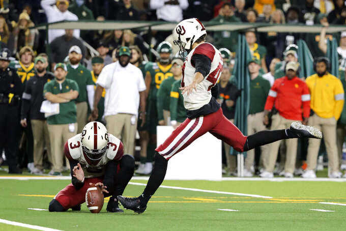 Oklahoma place kicker Gabe Brkic, right, kicks a 28-yard field goal as Connor McGinnis holds during the second half of an NCAA college football game against Baylor in Waco, Texas, Saturday, Nov. 16, 2019. (AP Photo/Ray Carlin)