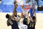 Kentucky's Davion Mintz, second from left, shoots while pressured by Notre Dame's Juwan Durham (11), Nate Laszewski (14) and Cormac Ryan (5) during the second half of an NCAA college basketball game in Lexington, Ky., Saturday, Dec. 12, 2020. Notre Dame won 64-63. (AP Photo/James Crisp)