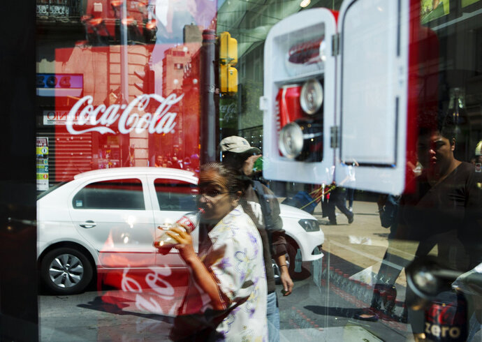 FILE -  In this Oct. 9, 2014 file photo, a woman is reflected in a Coca-Cola store window display as she drinks a Coke in Mexico City. Mexicans are among the biggest soda drinkers in the world, so residents of the southern city of Ciudad Altamirano were hit hard when first Coca-Cola then Pepsi closed their distribution centers amid drug gang extortion demands. (AP Photo/Rebecca Blackwell, File)