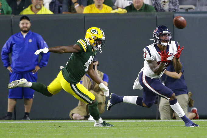 Houston Texans wide receiver Tyron Johnson makes a catch while being covered by Green Bay Packers defensive back Nydair Rouse during the second half of an NFL preseason football game Thursday, Aug. 8, 2019, in Green Bay, Wis. (AP Photo/Jeffrey Phelps)