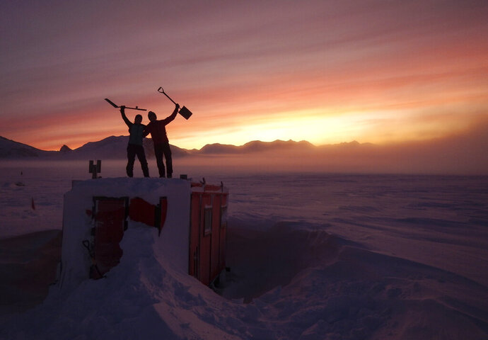 In this handout photo provided by British Antarctic Survey, field guides Sarah Crowsley, left, and Sam Hunt, right, pose for a photo after digging out the caboose, a container used for accommodation that can be moved by a tractor, at Adelaide island, in Antarctica on Friday, June 19, 2020. Antarctica remains the only continent without COVID-19 and now in Sept. 2020, as nearly 1,000 scientists and others who wintered over on the ice are seeing the sun for the first time in months, a global effort wants to make sure incoming colleagues don't bring the virus with them. (Robert Taylor/British Antarctic Survey via AP)
