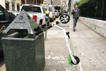 In this photo taken May 14, 2018, a man walks past an electric scooter that was dumped into a trash can in San Francisco. Tired of San Francisco streets being used as a testing ground for the latest delivery technology and transportation apps, city leaders are considering requiring businesses to get permits before trying out new high-tech ideas in public. Supporters of the legislation, which the Board of Supervisors will take up Tuesday, Dec. 10, 2019, say it would be the first of its kind in the U.S. They say it's long overdue in a city that's a hub for major tech companies but is more accustomed to reacting to the sudden arrival of new technology, such as when hundreds of dockless electric scooters appeared overnight last year. (AP Photo/Janie Har)