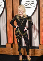 In this Saturday, Oct. 12, 2019, photo Dolly Parton poses for the camera before a press conference at her 50th Opry Member Anniversary at the Grand Ole Opry in Nashville, Tenn. The73-year-old actress, singer and songwriter, who first played the Opry when she was just a teenager, celebrated her 50th anniversary as a Grand Ole Opry member on Saturday. (Larry McCormack/The Tennessean via AP)
