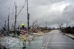 Trees destroyed by Hurricane Dorian line a road as a man walks by, in Abaco, Bahamas, Monday, Sept. 16, 2019. Dorian hit the northern Bahamas on Sept. 1, with sustained winds of 185 mph (295 kph), unleashing flooding that reached up to 25 feet (8 meters) in some areas. (AP Photo/Ramon Espinosa)