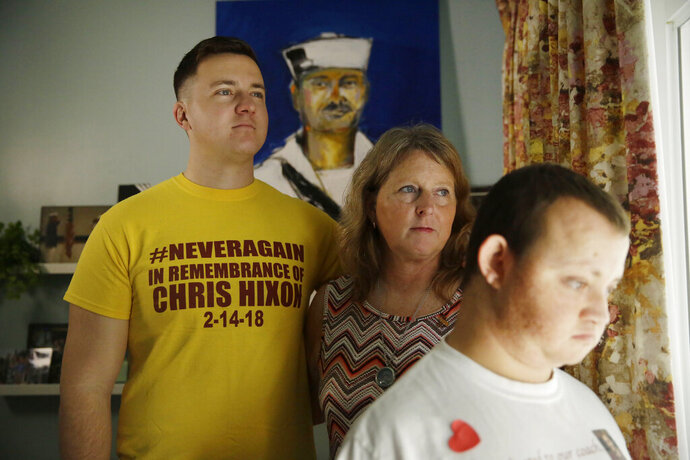 The Hixon family, Tom, Debbi, and Corey, pose for a portrait in front of a painting of Chris Hixon, a Parkland school shooting victim on Friday, Feb. 14, 2020, in Hollywood, Fla. Chris Hixon was killed in a school shooting on Valentine's Day two years ago at Marjory Stoneman Douglas High School. His widow Debbi recently had the family home renovated by the program