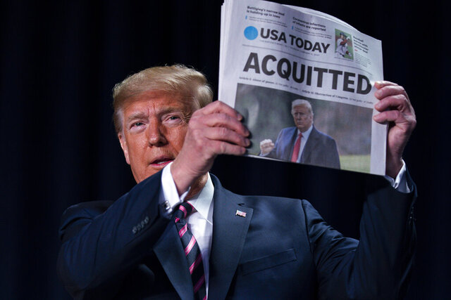 FILE - In this Feb. 6, 2020, file photo, President Donald Trump holds up a newspaper with the headline that reads