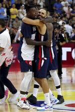 France's Mathias Lessort at left hugs France's Evan Fournier as they celebrate defeating United States during a quarterfinal match for the FIBA Basketball World Cup in Dongguan in southern China's Guangdong province on Wednesday, Sept. 11, 2019. France defeated United States 89-79. (AP Photo/Ng Han Guan)