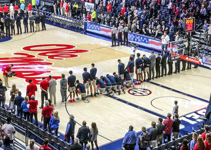 FILE - In this Saturday, Feb. 23, 2019, file photo, several Mississippi basketball players take a knee during the national anthem before an NCAA college basketball game against Georgia in Oxford, Miss. Mississippi Gov. Phil Bryant says he hasn't given much thought about the University of Mississippi basketball players who kneeled during the National Anthem to protest a pro-Confederate gathering on campus.  (Nathanael Gabler/The Oxford Eagle via AP, File)