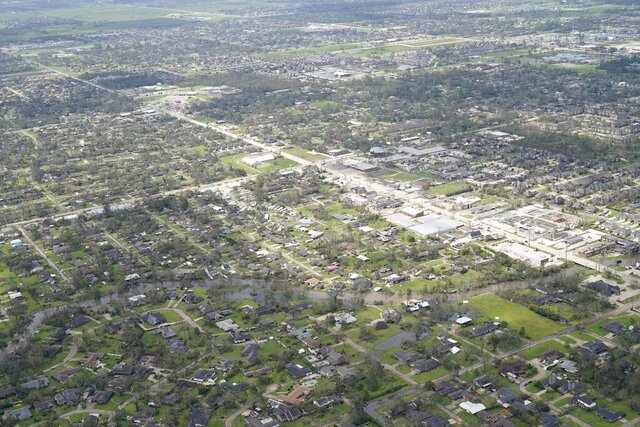 Blown down trees and debris surround damaged homes and buildings in the aftermath of Hurricane Laura Thursday, Aug. 27, 2020, near Lake Charles, La. (AP Photo/David J. Phillip)
