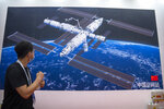 A visitor looks at a mural showing an artist's rendering of China's space station at the World Robot Conference in Beijing, Saturday, Sept. 11, 2021. Three Chinese astronauts have departed from the country's orbiting space station in preparation for returning to Earth after 90 days in orbit, the national space agency reported Thursday, Sept. 16, 2021.  (AP Photo/Mark Schiefelbein)