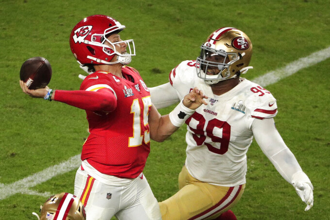 Kansas City Chiefs quarterback Patrick Mahomes (15) aims a pass to Tyreek Hill (10) as San Francisco 49ers' DeForest Buckner (99) attempts to defend, during the second half of the NFL Super Bowl 54 football game Sunday, Feb. 2, 2020, in Miami Gardens, Fla. (AP Photo/Charlie Riedel)