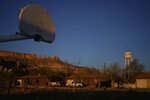 FILE - In this Sunday, April 19, 2020, file photo, the water tower and a basketball backboard at the school in Chilchinbeto, Ariz., on the Navajo reservation, are seen at sunrise. Basketball is woven in the fabric of Native American life. Now, during a global pandemic, the balls have all but stopped bouncing. Already hit hard by the coronavirus outbreak, Native Americans are faced with life without basketball — or any other sport - for the forseeable future. (AP Photo/Carolyn Kaster, File)