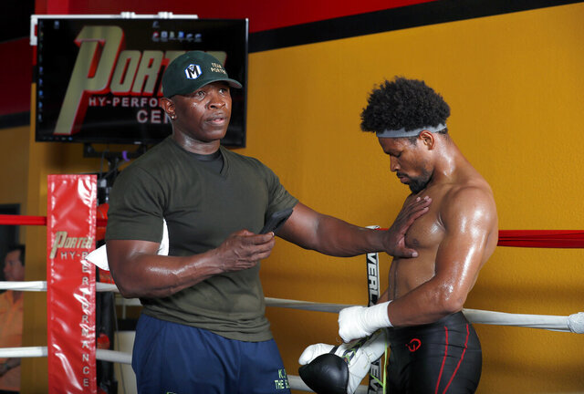 FILE - In this Aug. 15, 2018, file photo, father and trainer Kenny Porter checks the heart rate of welterweight boxer Shawn Porter after a workout in Las Vegas. Shawn Porter needed a place to train, and someone to fight. His father, Kenny, gave him both during the pandemic lockdown. (Steve Marcus/Las Vegas Sun via AP, File)