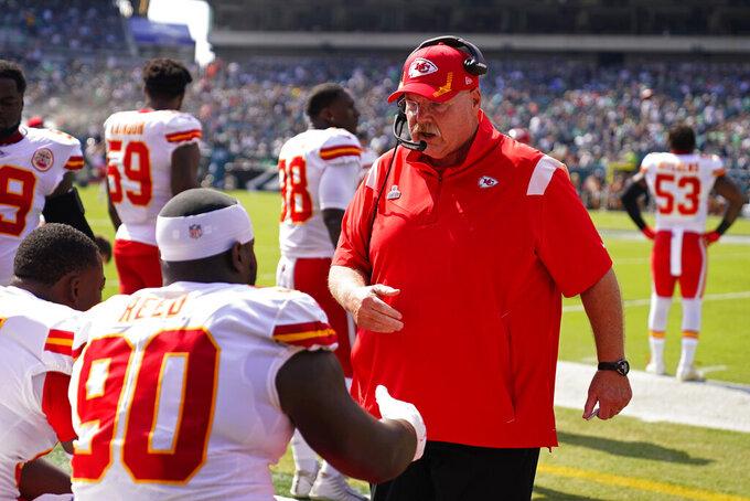 Kansas City Chiefs head coach Andy Reid talks to Kansas City Chiefs defensive tackle Jarran Reed (90) before an NFL football game against the Philadelphia Eagles on Sunday, Oct. 3, 2021, in Philadelphia. (AP Photo/Matt Rourke)