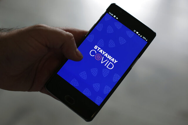 A man shows the contact tracing app Stayaway Covid on his cellphone, in Lisbon, Thursday, Sept. 17, 2020. The smartphone app uses Bluetooth technology to help discover whether people have been in close proximity to someone infected with COVID-19. Mobile apps tracing new COVID cases were touted as a key part of Europe's plan to beat the coronavirus outbreak. Seven months into the pandemic, virus cases are surging again and the apps have not been widely adopted due to privacy concerns, technical problems and lack of interest from the public. (AP Photo/Armando Franca)
